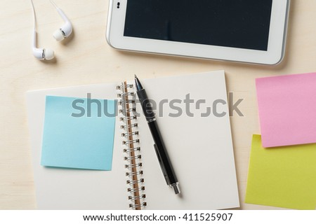 Sticky paper with blank area for text or message, opened notebook,and pen beside small tablet pc and in ear headset on wood table - stock photo