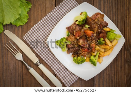 Stifado - a traditional Cypriot dishes, spread in Greece. It consists of a stew with tomatoes, potatoes, broccoli, onions, garlic and spicy spices. Wooden rustic table. Top view. Close-up - stock photo