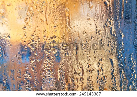 Stiffened rain drops on windowpane at sunset.  - stock photo