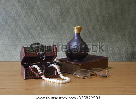 Stil life with old chest ,pearl necklace and different objects on wooden table. - stock photo