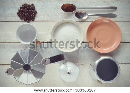 Still life. A dismounted kettle next to some sugar and a coffee cup. Coffee beans and ground coffee on a white wooden table. Top view. - stock photo