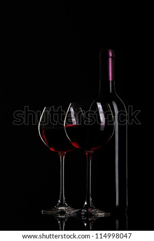 still-life arrangement: bottle of wine and a glass wine on black background - stock photo