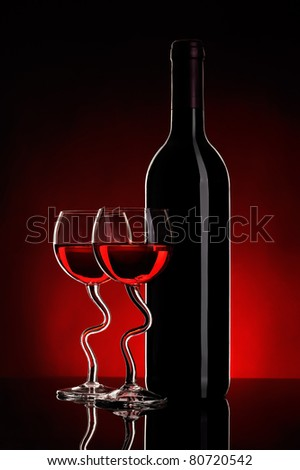 still-life arrangement: bottle of wine and two glasses wine on red background - stock photo