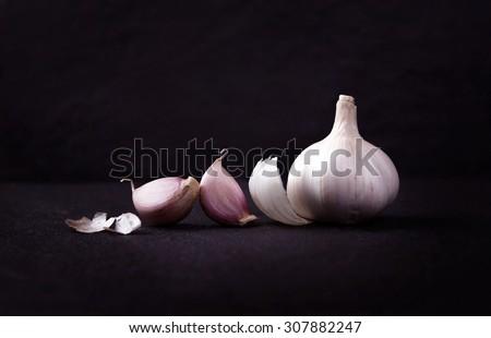 still life arrangement of Three whole garlic bulbs grouped on black stone plate - stock photo