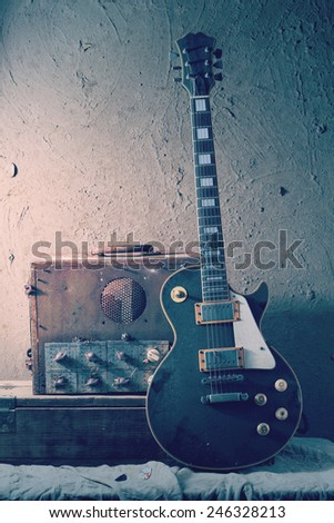 Still life art photography of vintage electric guitar and rare vintage amplifier on grunge background - stock photo