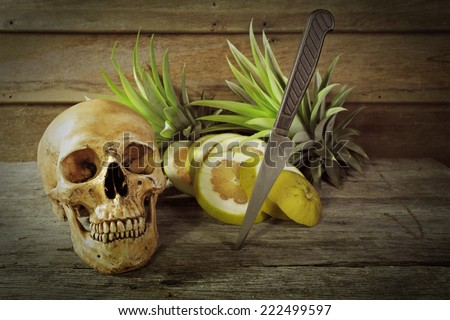 Still life art photography on fruits with human skull death concept - stock photo