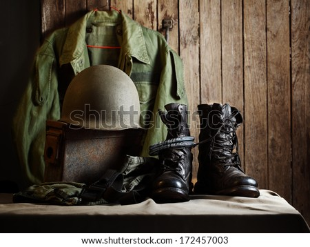 Still life art photography on vintage army jacket field coach helmet jungle boots and metal bullets box - stock photo