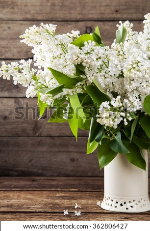 Still life. Bouquet of white lilacs in a vase on a wooden table. Rustic style and selective focus. Toned. - stock photo