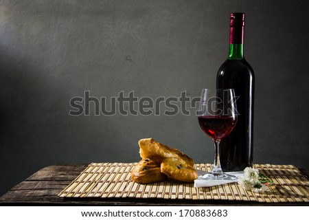 still life bread and wine on the background of old pictures. - stock photo