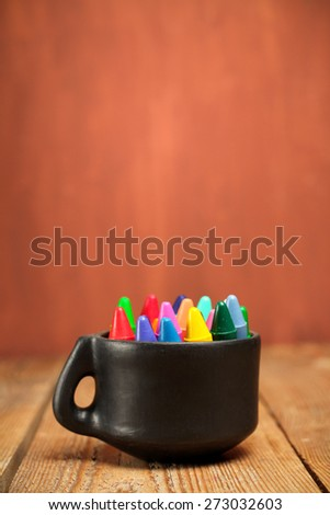 Still life, business, education concept. Crayons in a mug on a wooden table. Selective focus - stock photo