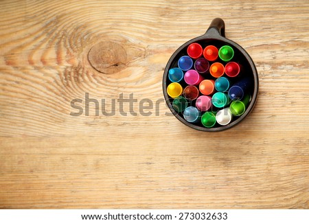 Still life, business, education concept. Crayons in a mug on a wooden table. Selective focus, top view, copy space background - stock photo