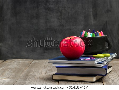 Still life, business, education concept. Crayons (pencils) in a mug, notebooks and apple on a wooden table with chalkboard. Selective focus, copy space, school background - stock photo