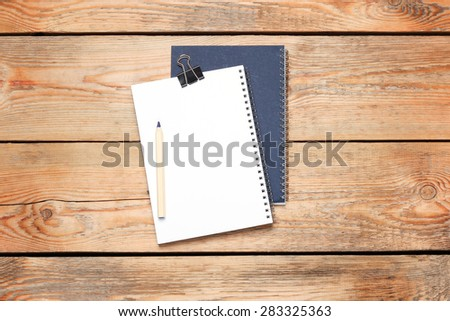 Still life, business, education concept. Office supplies, notepad and a pencil on a wooden table. Selective focus, copy space background, top view - stock photo
