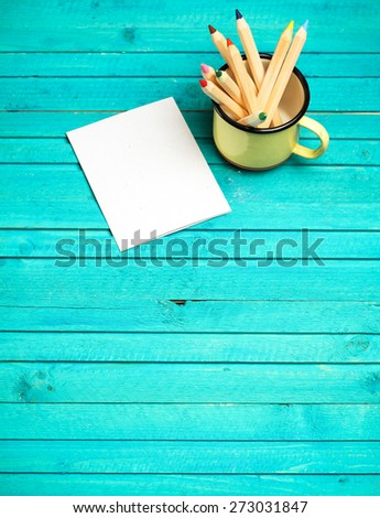 Still life, business, education concept. Pencils in a mug with notepad on a wooden table. Selective focus, copy space background, top view - stock photo