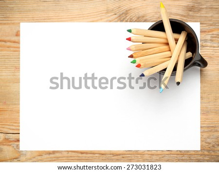 Still life, business, education concept. Pencils in a mug with sheet of paper on a wooden table. Selective focus, copy space background, top view - stock photo