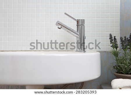 Still life close up detail of a bathroom sink and tap against a mosaic tile wall in a white bath room at home, interior. Aspirational living bathroom washing sink in a quality luxury home, indoors. - stock photo