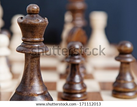 Still life close up detail view of a queen chess dark wooden piece on a chess board while a strategic game is being played. Interior professional strategy game playing. - stock photo