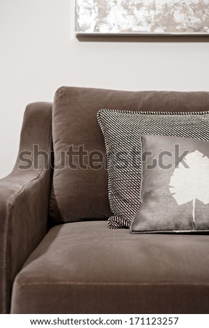 Still life close up view of an elegant brown sofa in a luxury home living room with different natural fabrics cushions and textures. Hotel interior suite detail. - stock photo