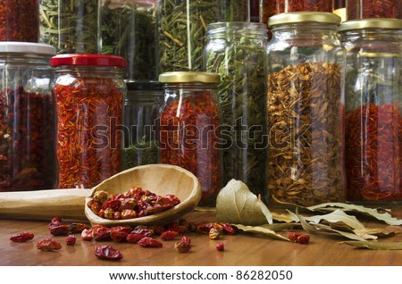 still life composition of many different spices teas and herbs on a wooden table - stock photo