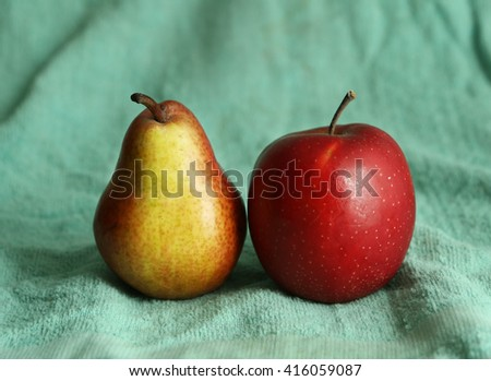 still life composition with apple and pear on blue cloth background - stock photo
