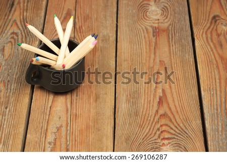 Still life concept. Pencils in a mug on a wooden table. Selective focus, copy space background - stock photo