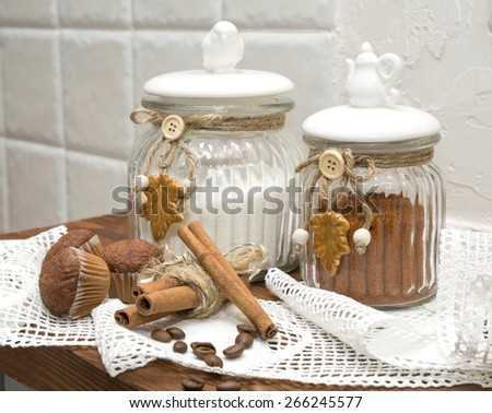 still life, decorative jars for bulk products with cupcakes and cinnamon on a background of lace - stock photo