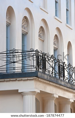 Still life detail of a classic centenary stone building with decorative arch window frames and iron design banister on solid columns in the city of London. Architectural detail of power, outdoors. - stock photo