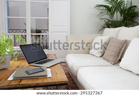 Still life detail view of a luxurious living room with sofa, an open laptop computer with blank screen and a smartphone with paperwork, home interior. Aspirational technology indoors lifestyle. - stock photo
