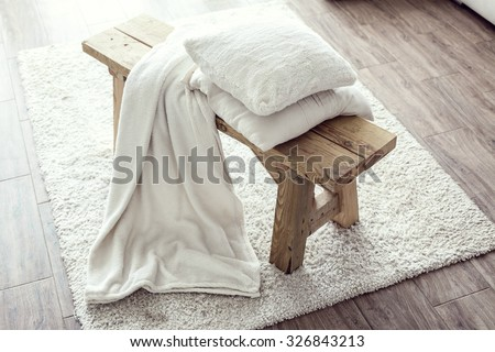 Still life details, stack of white cushions and blanket on rustic bench on white carpet - stock photo