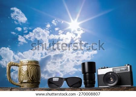 still life details, sunglasses, camera, beer mug, lens on wood table - stock photo