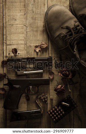 Still Life Disassembled handgun ,Bullet ,Boots, Rose and wood space on wood floor.Top view , Dark tone picture style - stock photo