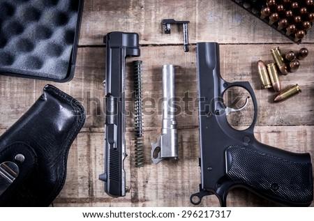 Still Life Disassembled handgun ,Bullet on wood floor.Top view , Vintage Style - stock photo