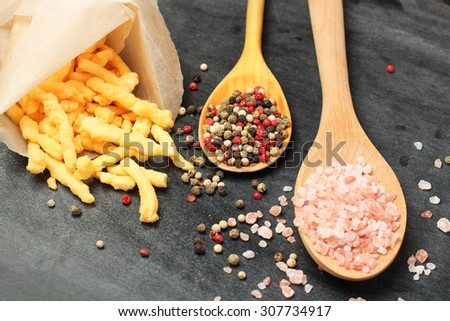 Still life, food and drink concept. Corn cheese puffs with himalayan rose salt and pepper on a black chalkboard. Selective focus, copy space background, top view - stock photo