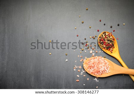 Still life, food and drink concept. Himalayan rose salt and pepper on a black chalkboard. Selective focus, copy space background, top view - stock photo