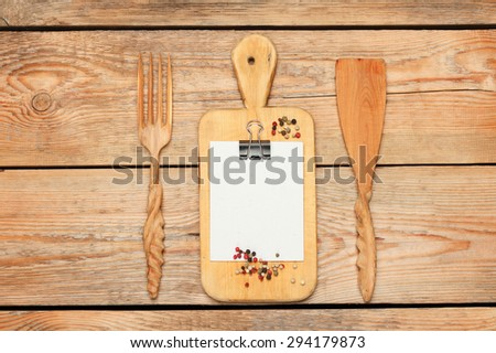 Still life, food and drink concept. Kitchen cooking utensils (knife, fork, cutting board, paper for recipe) on a wooden table. Selective focus, copy space background, top view - stock photo