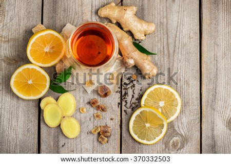Still life, food and drink, healthcare concept. Ginger tea and ingredients on a rustic wooden table. Selective focus, top view, copy space background - stock photo