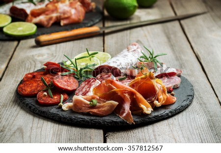Still life, food and drink, holidays concept. Assortment of spanish tapas or italian antipasti  (jamon, prosciutto, chorizo, salami) on a grunge black board (rustic style). Selective focus - stock photo
