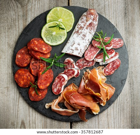 Still life, food and drink, holidays concept. Assortment of spanish tapas or italian antipasti  (jamon, prosciutto, chorizo, salami) on a grunge black board (rustic style). Selective focus, top view - stock photo