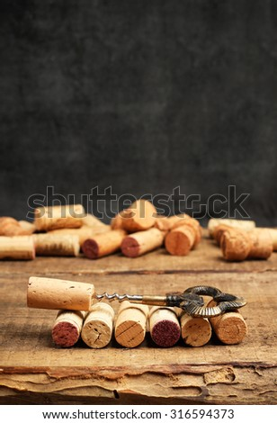 Still life, food and drink, holidays concept. Wine corks and corkscrew on a wooden table. Selective focus, copy space chalkboard - stock photo