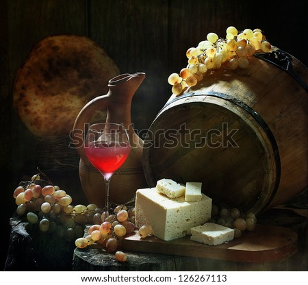 Still-life, fragrant pink wine a graceful glass with salty house cheese and ripe sweet grapes - stock photo