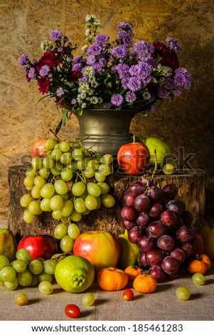 Still Life Fruits were placed on the timber with a beautiful vase of flowers. - stock photo