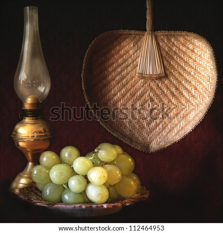 Still life, grapes, oil lamp and fan - stock photo
