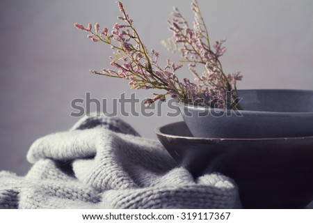 Still life gray vintage bowls with pink flowers and woolen scarf horizontal - stock photo