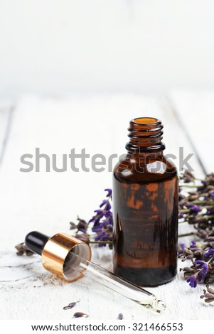Still life, health and beauty, spa concept. Dry lavender and oil  on a white wooden table. Selective focus, copy space background - stock photo