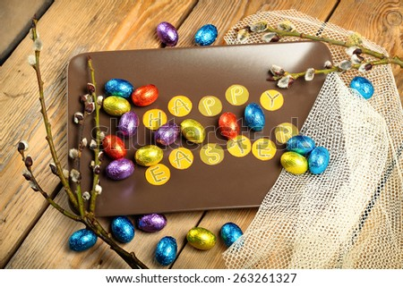 Still life, holidays, food and drink concept. Easter decoration with chocolate eggs and willow branch. Top view, selective focus - stock photo