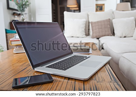 Still life home interior of elegant spacious family living room with a stylish coffee table and a laptop computer and smartphone device, house living indoors. Aspirational technology and lifestyle. - stock photo