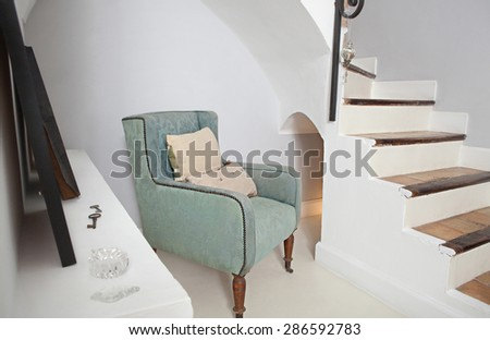Still life home interior view of a traditional quality wooden armchair with cushions in a home living room with stairs, indoors. Elegant reading room with upholstery chair, aspirational lifestyle. - stock photo