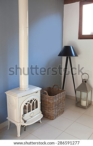 Still life home interior view of a traditional quality wrought iron fireplace stove in a stylish home living room, indoors. Elegant stylish standing lamp, empty space, aspirational lifestyle. - stock photo