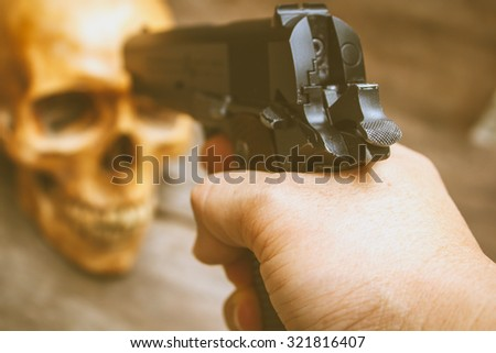 Still life human skull and gun ready to shoot. - stock photo