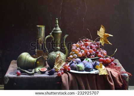 Still-life in east style with a beautiful jug both a ripe fig and juicy grapes - stock photo